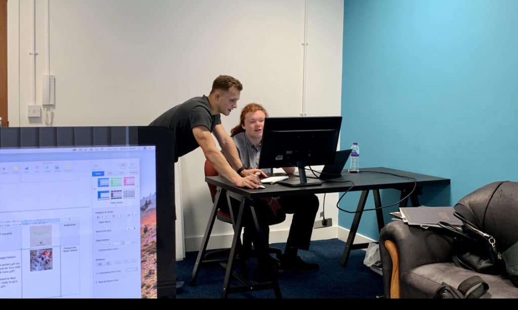 Founder of Beanie Media, Dan Atkinson stood at desk with web design apprentice Charlie